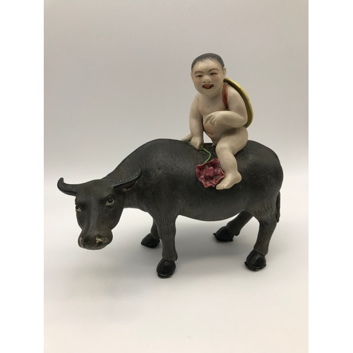 An Antique Chinese porcelain nude boy figure riding on top