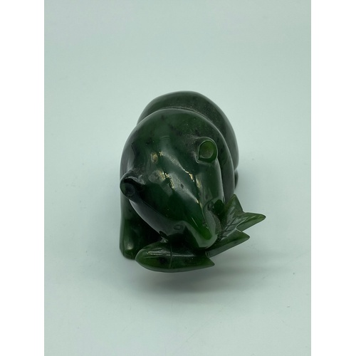 7 - A Oriental Hand carved Jade bear holding a fish within its mouth sculpture. Measures 4x6.5x4cm...