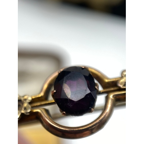 2J - A Ladies antique 9ct gold bar brooch set with three seed pearls [one missing] and a large Amethyst s...