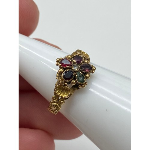 18J - A 19th century ladies gold ring set with various gem stones. Off set by a gold shell to each shoulde...