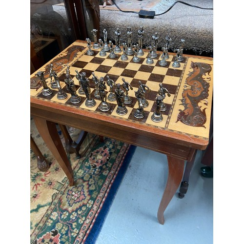 288A - A Vintage inlaid music chess top table together with Greek cast metal chess set and wooden carved se...