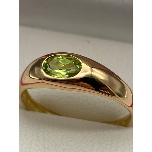 24 - A ladies 18ct gold ring set with a single green cut stone [Ring size 0] [Not hallmarked, tested usin...