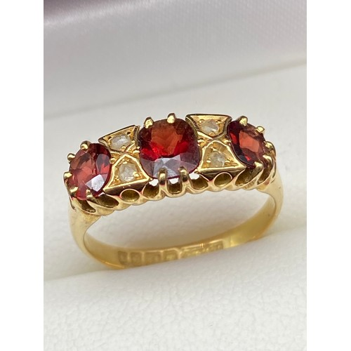 3J - A Lovely example of a ladies 18ct gold ring set with three large garnets and 4 small diamonds. [Ring...