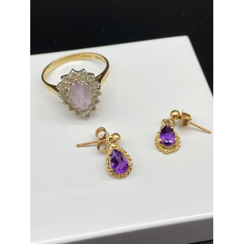 8J - A 9ct gold ladies ring set with a pale purple tear drop stone surrounded by clear stones, Together w...