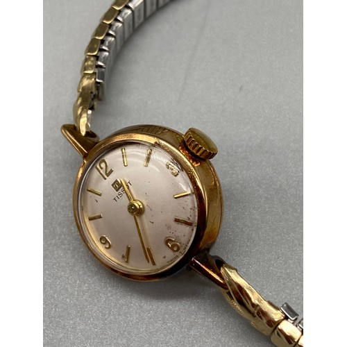 21J - A 9ct gold cased 'Tissot' ladies 17 Jewels watch with a plated flexible wrist band. In a running con...