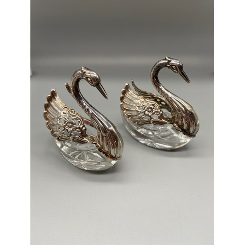 26 - A Pair of Import London silver swan salt dishes. Designed with articulated wings and crystal cut bod...
