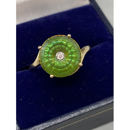 37 - An exquisite designed ladies 9ct/10K gold ring. Designed with a large green round cut stone with a s...
