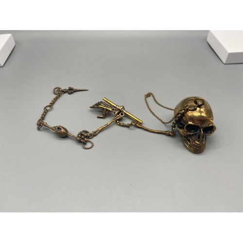 45 - A Brass Albert style watch chain with skull locket pendant....