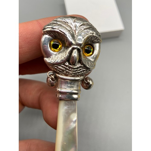 64J - A Sterling silver babies rattle in the form of an owls head. Finished with a mother or pearl handle.