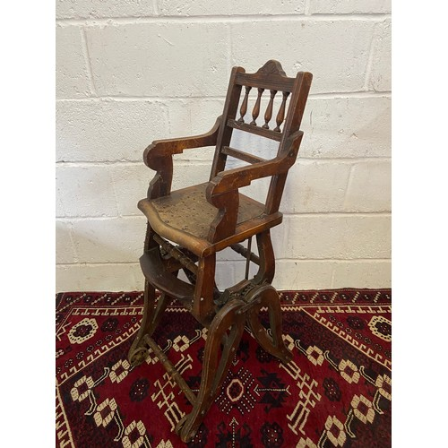 15C - A 19th century child's high chair, which converts to a rocker. Made from wood and mechanical movemen...