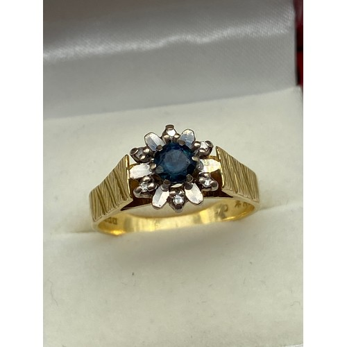14A - A Ladies 18ct gold single sapphire and 6 small diamond stone ring. Designed like a flower. [5.09gram...