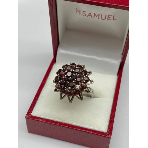 29A - A Ladies silver and garnet cluster ring. [Ring size M]...