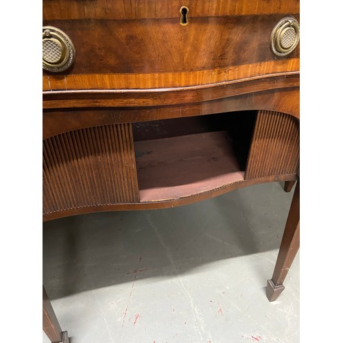 26 - Georgian Style Mahogany Serpentine sideboard. A Serpentine top above a central frieze drawer and arc...