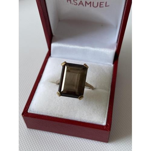 34J - A 9ct gold ring set with a smokey quartz cut stone ring [size Q] [4.98g]...