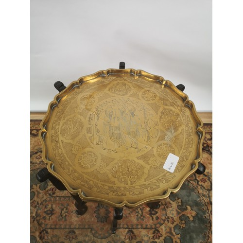 45 - A brass tea tray table with scalloped edging, engraved in a Japanese theme, supported on a 6 arm/leg...