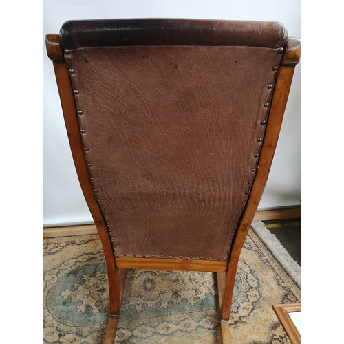 49 - A 19th century rocking chair with curved arms, raised on turned and square legs with applied rocker,...