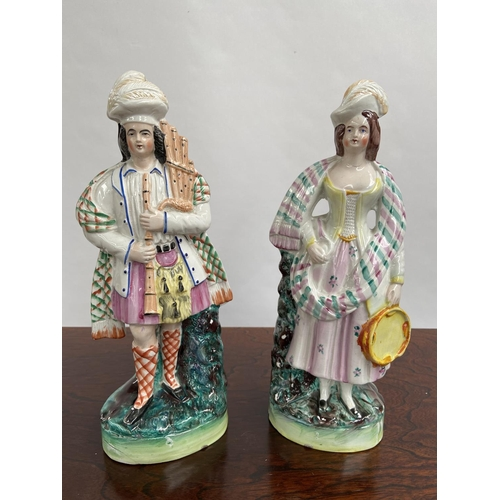 122 - A Pair of Antique Staffordshire Scottish man and lady figurine. Man playing bagpipes and the lady is...