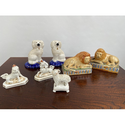 123 - A Collection of antique Staffordshire animal figurines to include a pair of lions, Ram on a pedestal...