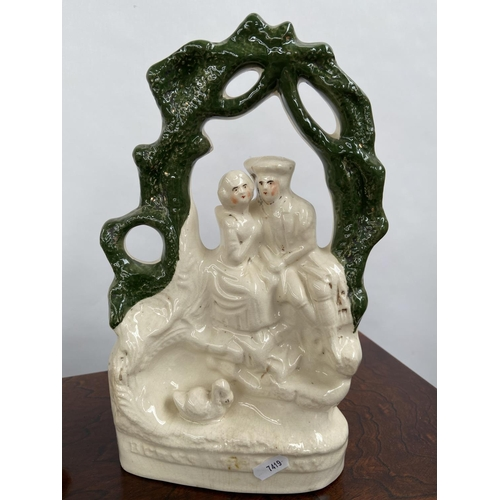 124 - A Lot of two Antique Staffordshire figurines to include Couple resting against a tree and Robbie bur...