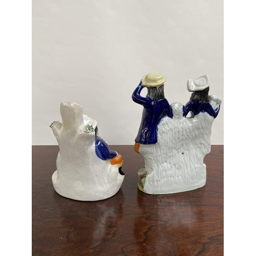 133 - Two various antique Staffordshire figurines to include clock design couple figurine and two gents re...