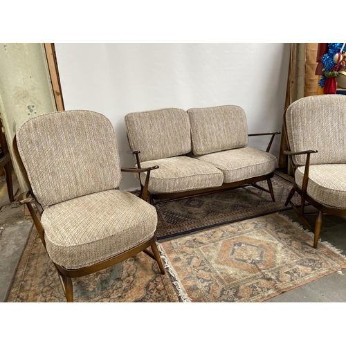 142 - A Vintage Ercol elm wood three piece cottage suite. [two seater 87x130x78cm] [Chairs 89x70x80cm]...