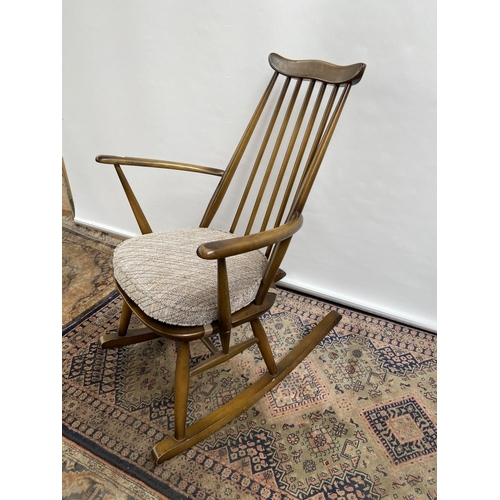 142A - A Vintage Ercol elm wood rocking arm chair. [87x61x43cm]...