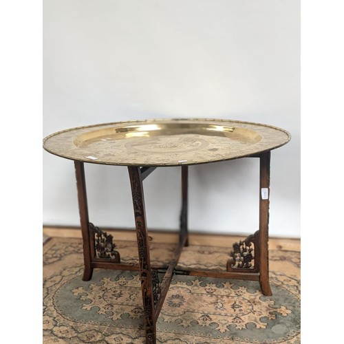 7 - A 19th century gilt brass tea table, engraved with Chinese story sections, upon a hand carved foldin...