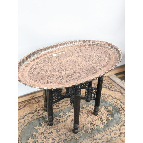 10 - A 19th century middle eastern copper tea table, with an oval shape and detailed with engravings to d...