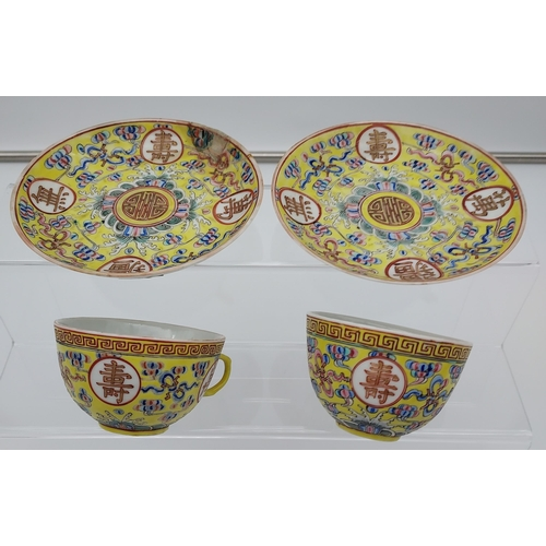 12 - Two Chinese cups and saucers in a yellow ground, Guangxu 1875-1908 signature to the base.