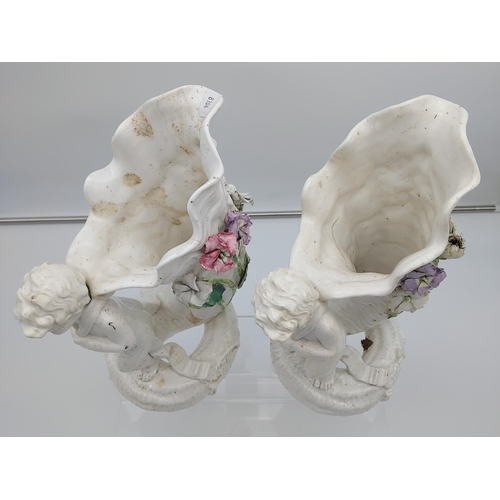18 - A Pair of 19th century Moore Bros cherub figurine carrying a horn shell vase. [Both as found] [29cm ...