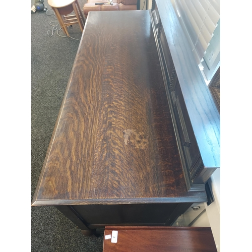 26 - An oak sideboard with raised back detailed with twist and bead decoration, two centre drawers with s...