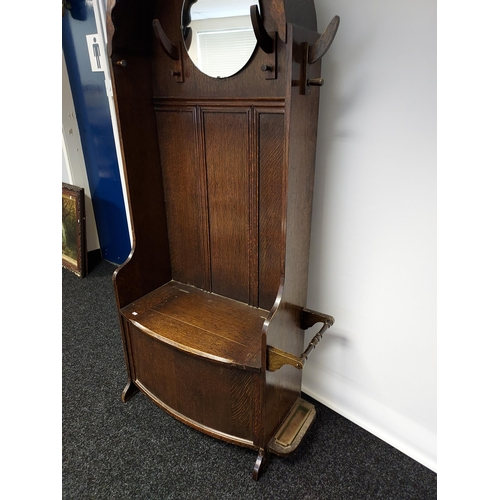 27 - A nice example of an Art Deco oak, hall coat stand. Designed with a circular mirror, and lift up sea...