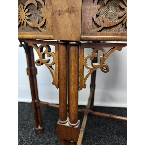 32 - A 19th century barrel window table with glass top above a carved frieze, supported on cluster column...