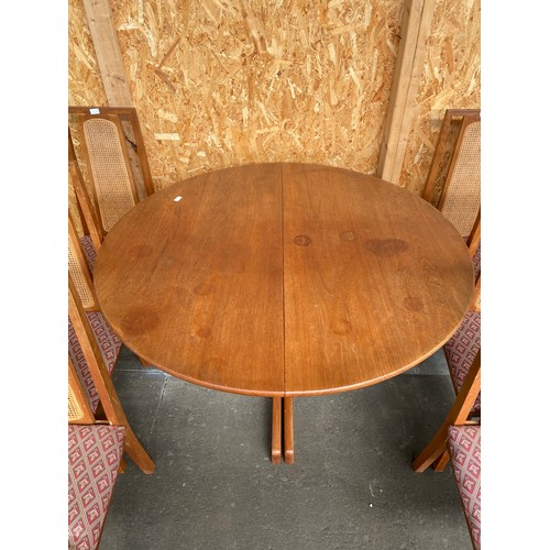 41 - A Mid Century Scandinavian style teak round table and 6 matching chairs. Comes with a leaf.