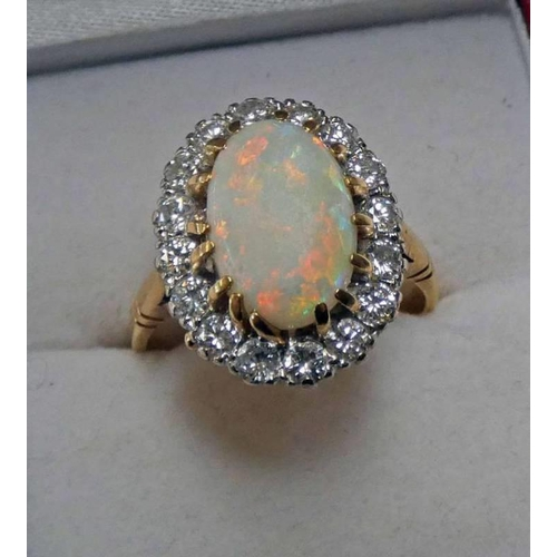 11 - 18CT GOLD OVAL OPAL & DIAMOND SET CLUSTER RING, THE DIAMONDS APPROX 0.80 CARATS IN TOTAL.