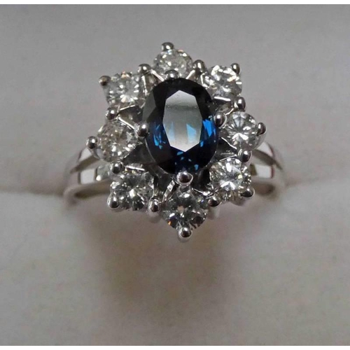 23 - SAPPHIRE & DIAMOND SET CLUSTER RING. THE OVAL SAPPHIRE IN A SURROUND OF BRILLIANT CUT DIAMONDS, THE ...