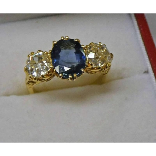43 - 18CT GOLD SAPPHIRE & DIAMOND 3 - STONE RING. THE OVAL SAPPHIRE OF APPROX 1.93 CARATS FLANKED BY 2 BR...