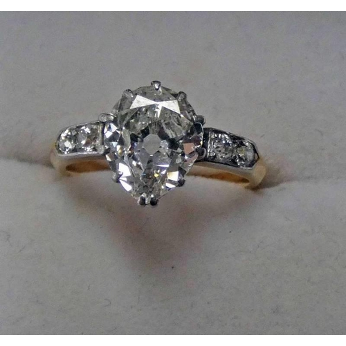 55 - A DIAMOND SINGLE STONE RING, THE PEAR-SHAPED DIAMOND SET BETWEEN SHOULDERS MOUNTED WITH OLD BRILLIAN...