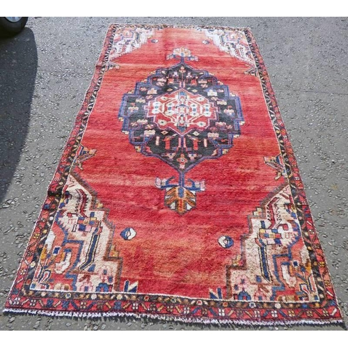 1050 - WASHED RED GROUND PERSIAN SAROUK RUG WITH A LARGE CENTRAL MEDALLION 270 X 132CM