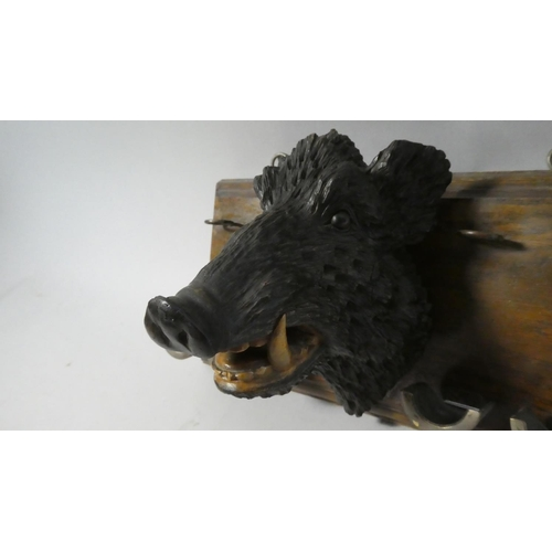 9 - A Nice Quality Black Forest Wall Hanging Pipe Rack with Carved Boar's Head and Four Brass Pipe Rests...