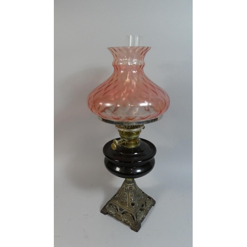 28 - A Late Victorian Iron Based Oil Lamp with Coloured Glass Reservoir and Shade, 56cm high...