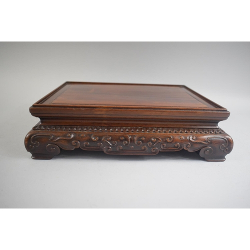 20 - A Good Quality Chinese Hardwood Rectangular Stand with Blind Carved Decoration and Four Scroll Feet....