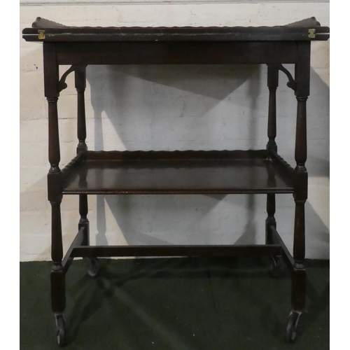 10 - An Edwardian Mahogany Two Tier Galleried Tea Trolley/Games Table with Lift and Twist Top Having Baiz...