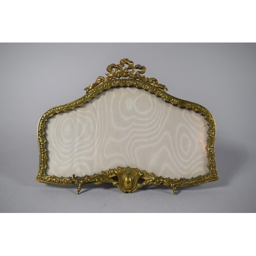 52 - A French Ormolu Shaped Easel Back Photo Frame with Ribbon Finial, 22cms Wide...