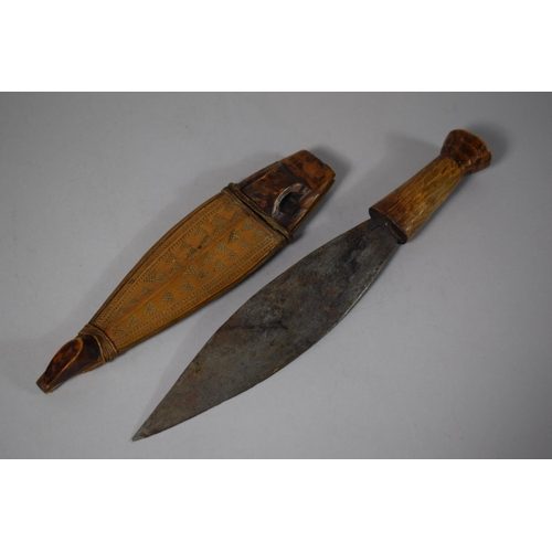 32 - A Tribal Dagger with Wooden Handle, Leaf Blade and Carved Wooden Scabbard, Blade 20.5cms Long...