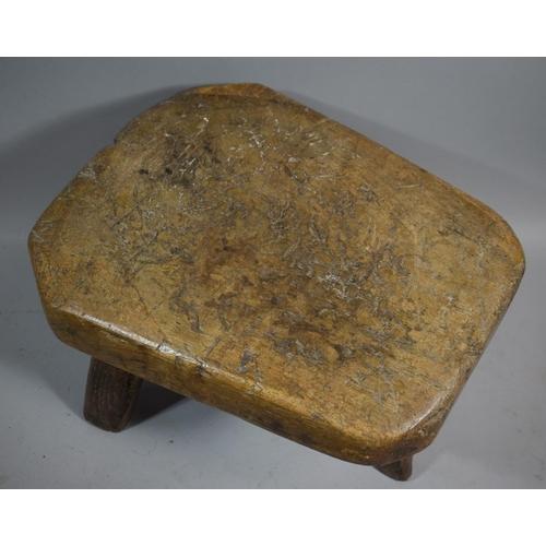 28 - An Early 19th Century Heavy Elm Topped Three Legged Pig Bench Stool, 55cms Long...