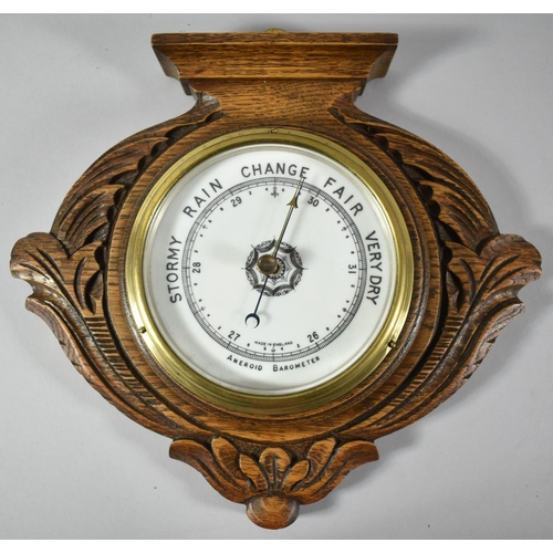 52 - An Edwardian Carved Oak Wall Hanging Aneroid Barometer with Brass Bezel, 28.5cm wide...