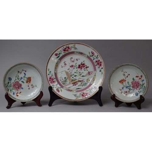 An 18th/19th Century Chinese Famille Rose Export Plate Decorated with Applied Enamels Depicting Exterior Garden Scene, 22cm Diameter, In Good Condition However Some Rubbing to Decoration, Together with Two Smaller Examples, One Having Nicks to Rim and both with Rubbing