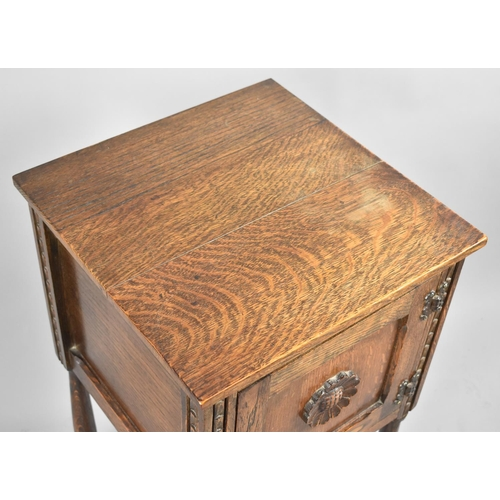21 - An Oak Bedside Cabinet with Carved Flower Decoration to Panelled Door, 41cm Square and 70cm high...