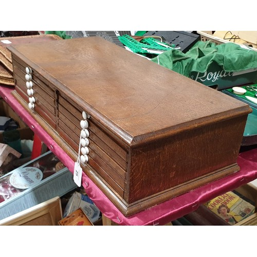 25 - An antique oak twelve drawer coin and medal collector's case having porcelain drawer pulls, width 21...